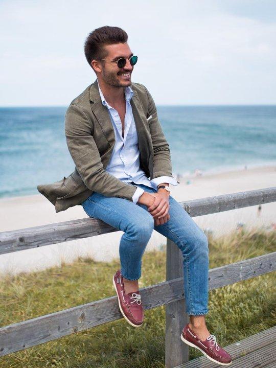 Vyras vilki žalią švarką, šviesiai mėlynus džinsus, avi raudonus batus