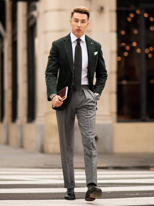 Vyras vilki žalią švarką, baltus marškinius, baltas kelnes