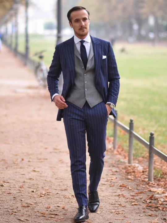Vyras vilki mėlyną kostiumą ir pilką liemenę