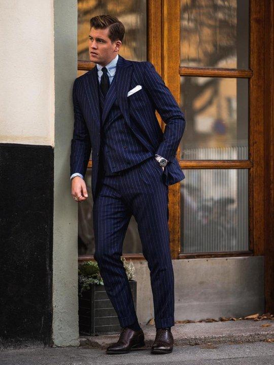 Vyras vilki mėlyną trijų dalių kostiumą