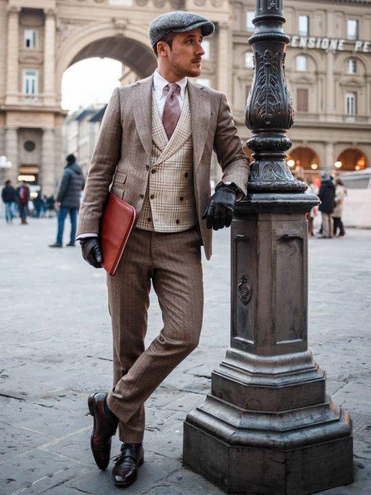 Vyras vilki šviesiai rudą kostiumą ir šviesiai rudą liemenę