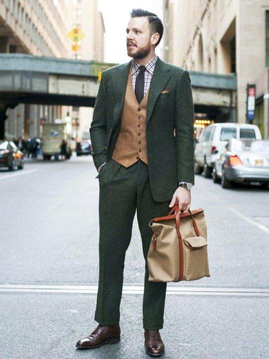 Vyras vilki žalią kostiumą ir šviesiai rudą liemenę