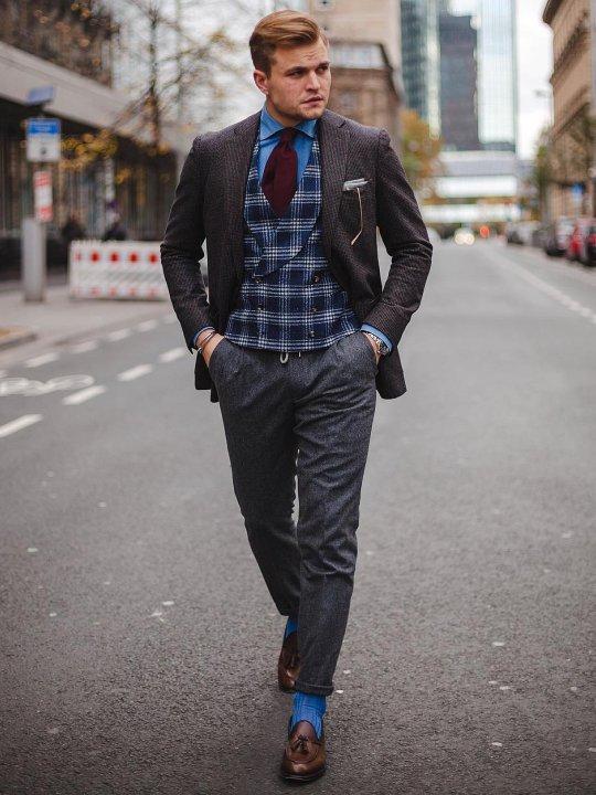 Vyras vilki rudą švarką, mėlyną languotą liemenę, pilkas kelnes