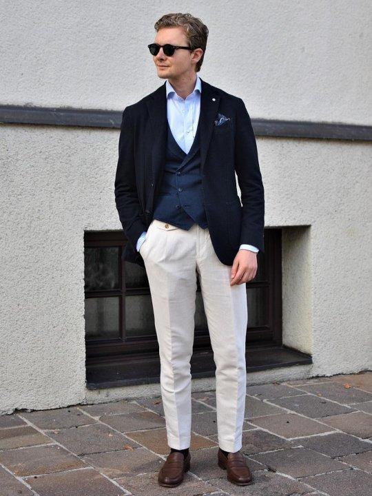 Vyras vilki tamsiai mėlyną švarką, mėlyną liemenę, baltas kelnes