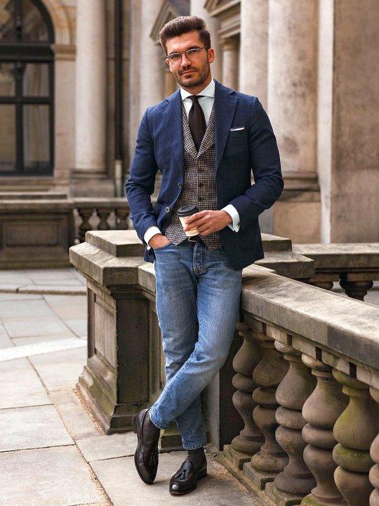Vyras vilki mėlyną švarką, rudą languotą liemenę, šviesiai mėlynus džinsus