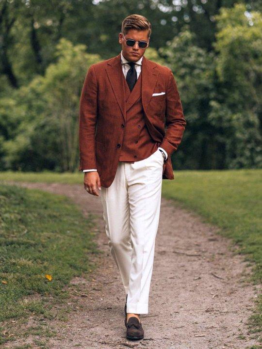 Vyras vilki rudą švarką, liemenę, baltas kelnes