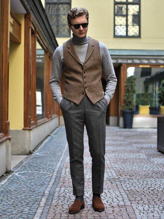 Vyras vilki rudą raštuotą liemenę, šviesiai pilką megztinį, tamsiai pilkas kelnes