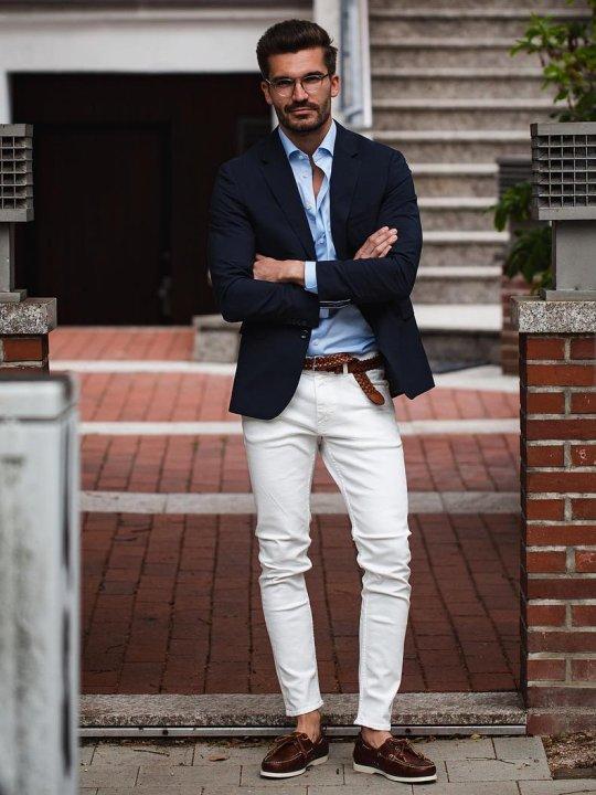 Vyras vilki mėlyną švarką ir baltus džinsus