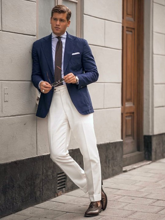 Vyras vilki mėlyną švarką ir baltas kelnes