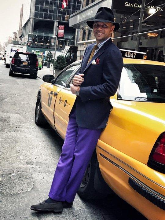 Vyras vilki mėlyną švarką ir violetines kelnes
