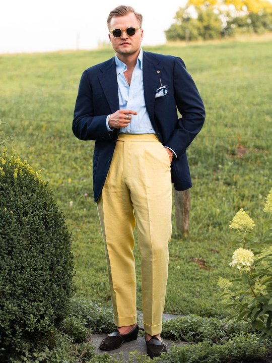 Vyras vilki mėlyną švarką ir geltonas kelnes