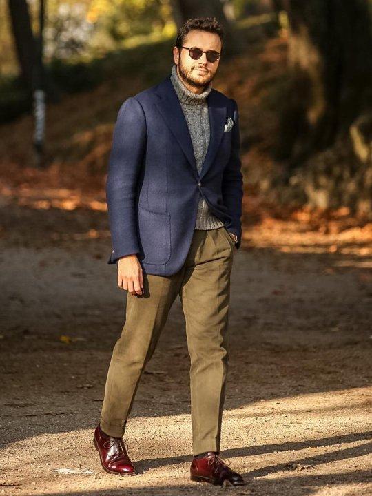 Vyras vilki mėlyną švarką, pilką megztinį, rudas kelnes