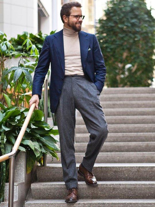 Vyras vilki mėlyną švarką, šviesų megztinį, pilkas kelnes