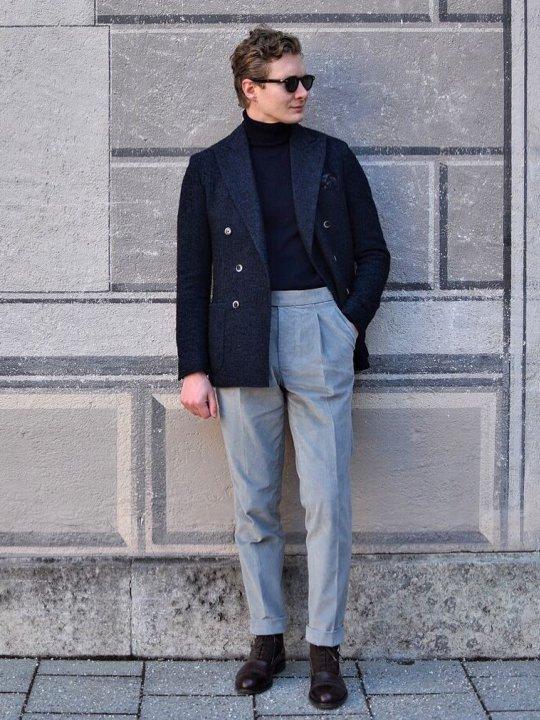 Vyras vilki mėlyną švarką, mėlyną megztinį, pilkas kelnes