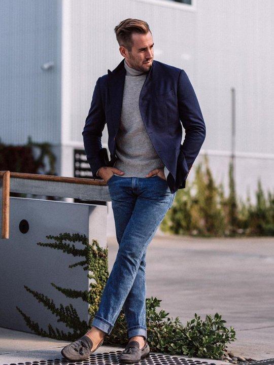 Vyras vilki mėlyną švarką, pilką megztinį, mėlynus džinsus