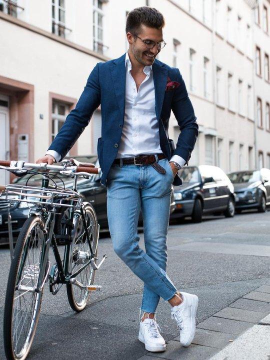 Vyras vilki mėlyną švarką ir šviesiai mėlynus džinsus