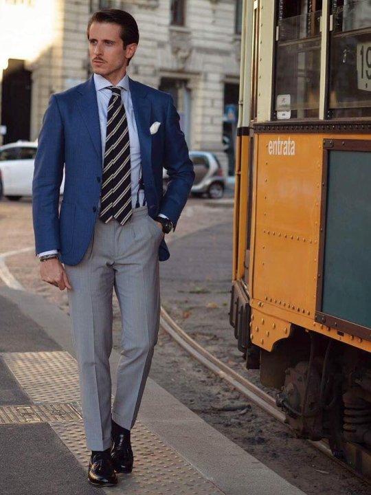 Vyras vilki mėlyną švarką, šviesiai mėlynus marškinius, šviesiai pilkas kelnes