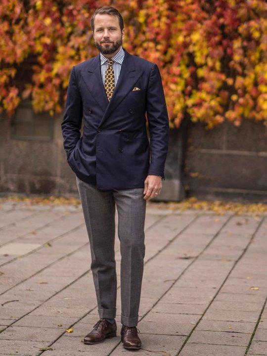 Vyras vilki mėlyną švarką, dryžuotus marškinius, pilkas kelnes