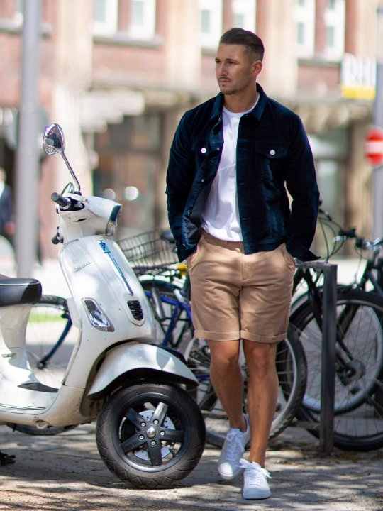 Vyras abi baltus sportinius batelius, mūvi šviesiai rudus šortus
