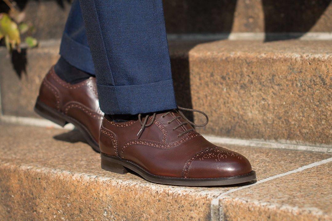 Mėlyno kostiumo ir rudų oksford batų derinys