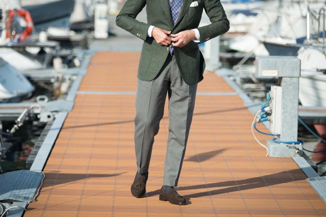 Vyras avi rudus batus, dėvi pilkas kelnes, žalią švarką
