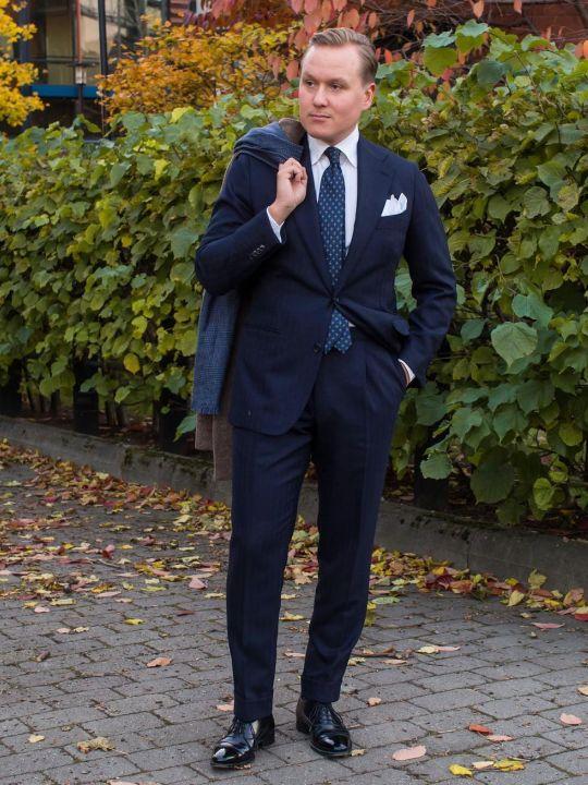 Vyras vilki mėlyną kostiumą, baltus marškinius, juodus batus