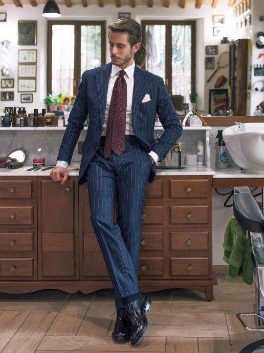 Vyras vilki mėlyną kostiumą, avi juodus derby batus