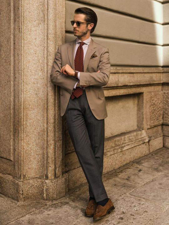 Vyras vilki šviesiai rudą švarką, tamsiai pilkas kelnes, avi rudus loaferius