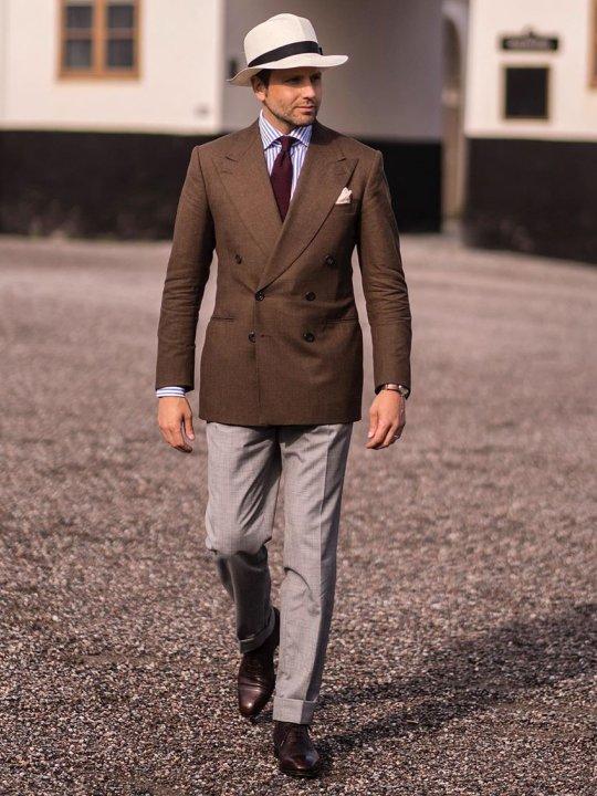 Vyras vilki rudą švarką, šviesiai pilkas kelnes, abi rudus derbius