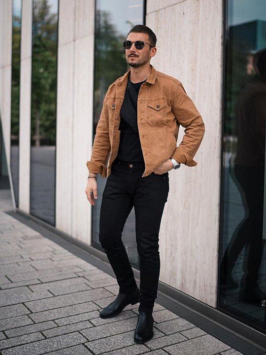 Vyras vilki šviesiai rudą striukę, juodus marškinėlius, mūvi juodus džinsus, avi juodus aulinius batus
