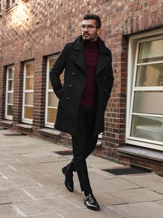Vyras vilki juodą paltą, tamsiai raudona megztinį, mūvi juodas kelnes, avi juodus batus