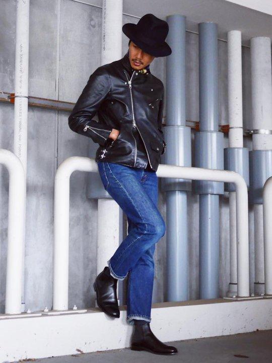 Vyras vilki juodą odinę striukę, mėlynus džinsus, avi juodus batus