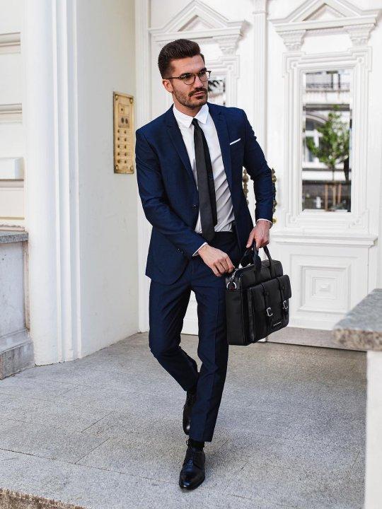 Vyras vilki mėlyną kostiumą, avi juodus batus