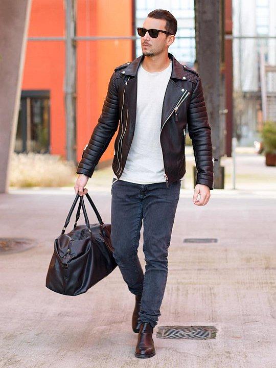 Vyras vilki juodą odinę striukę, baltus marškinėlius, pilkus džinsus, avi juodus batus