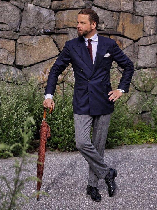 Vyras vilki tamsiai mėlyną švarką, pilkas kelnes, avi juodus batus