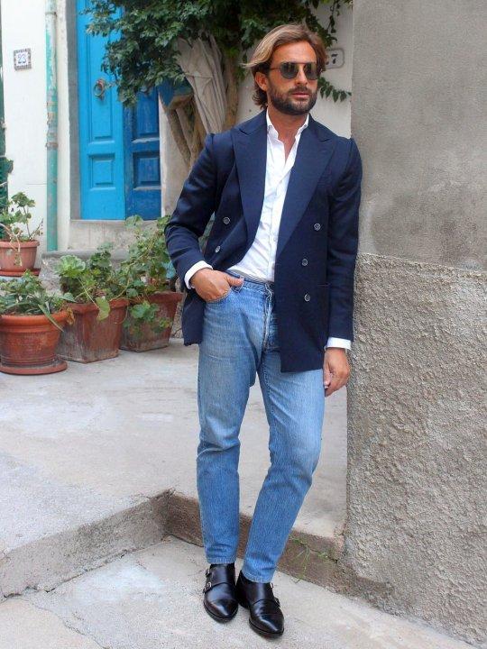 Vyras vilki mėlyną švarką, baltus marškinius, šviesiai mėlynus džinsus, avi juodus batus