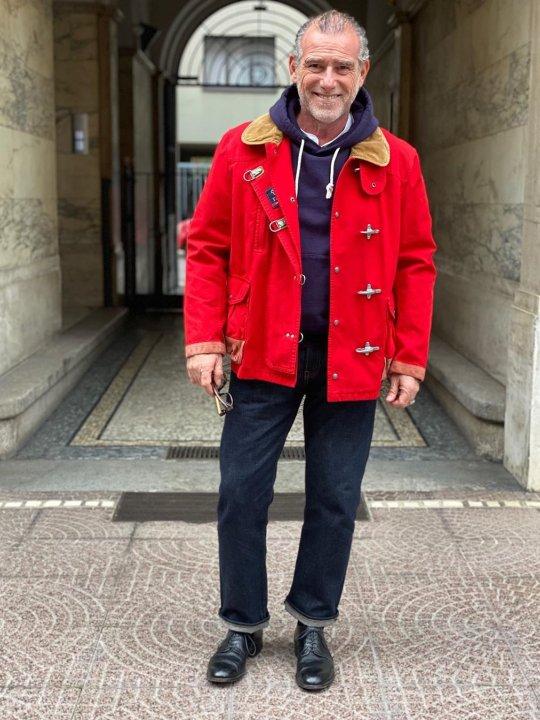 Vyras vilki raudoną striukę, tamsiai mėlynus džinsus, avi juodus batus