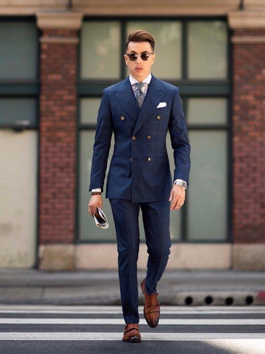 Vyras vilki mėlyną kostiumą, avi rudus batus