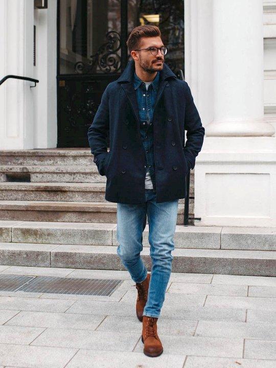 Vyras vilki tamsiai mėlyną paltą, šviesiai mėlynus džinsus, avi rudus aulinius batus