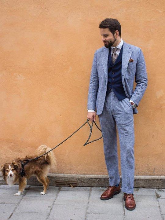 Vyras vilki šviesiai mėlyną kostiumą, avi rudus batus