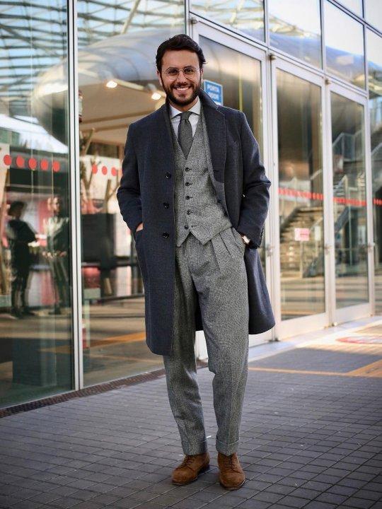 Vyras vilki tamsiai mėlyną paltą, šviesiai pilką kostiumą, avi rudus batus