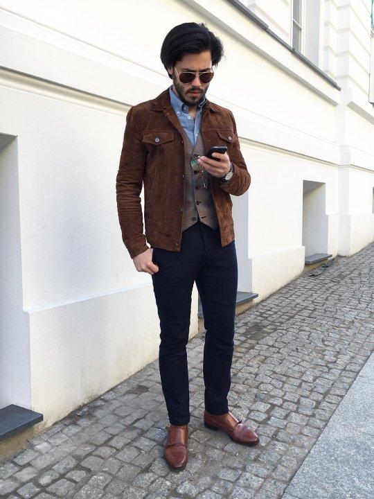 Vyras vilką rudą verstos odos švarką, tamsiai mėlynas kelnes, avi rudus batus