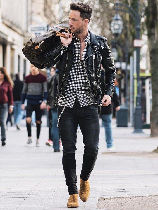 Vyras vilki juodą odinę striukę, juodus džinsus, avi šviesiai rudus batus