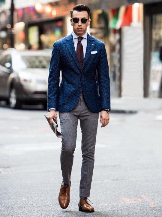 Vyras vilki mėlyną švarką, pilkas kelnes, avi šviesiai rudus batus