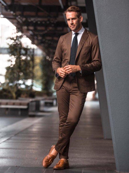 Vyras vilki rudą kostiumą, avi šviesiai rudus batus