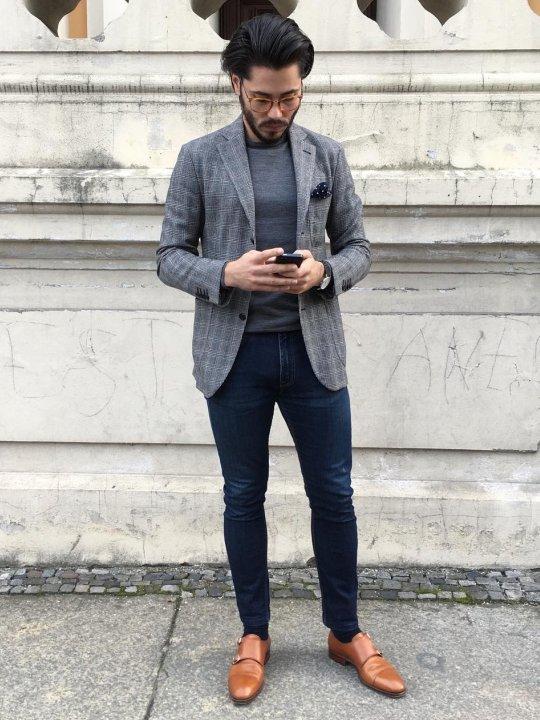 Vyras vilki pilką švarką, tamsiai mėlynus džinsus, avi šviesiai rudus batus