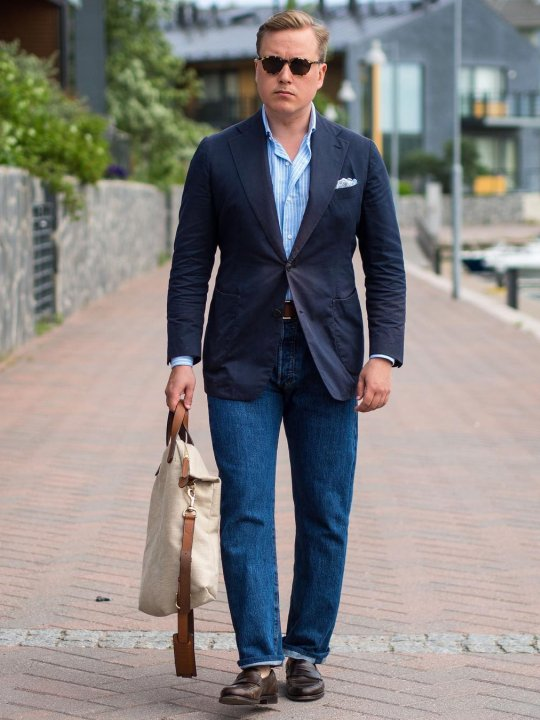 Vyras vilki mėlyną švarką, mėlynus džinsus, avi tamsiai rudus batus