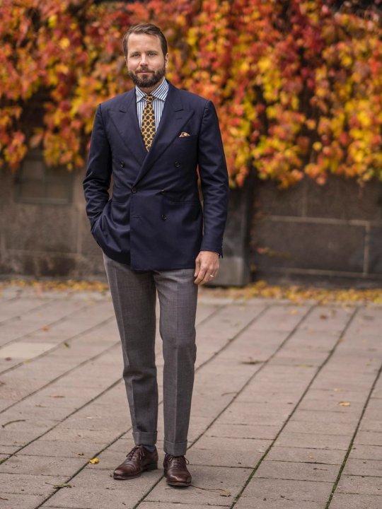 Vyras vilki mėlyną švarką, pilkas kelnes, avi tamsiai rudus batus