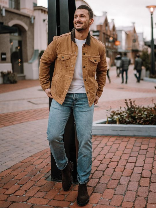 Vyras vilki šviesai rudą striukę, šviesiai mėlynus džinsus, avi tamsiai rudus batus