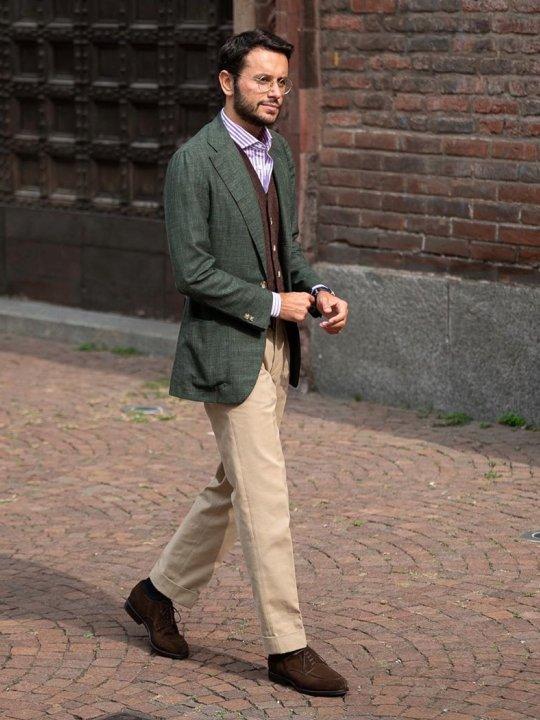 Vyras vilki žalią švarką, šviesiai rudas kelnes, avi tamsiai rudus batus